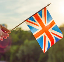 Hand holds Great Britainin flag an open window